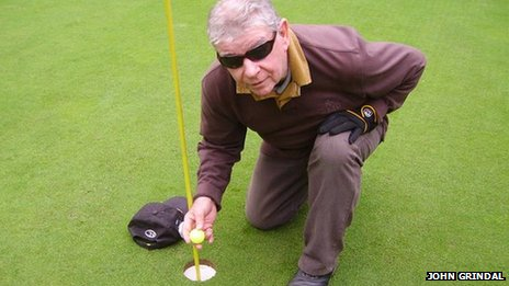 Image of Jim collecting his ball from the hole