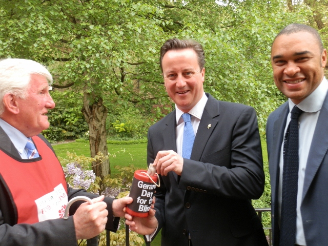 Pictured here is Tom receiving a donation from the PM David Cameron.